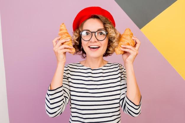 Dromerige schattige dame in rode baret met grote smakelijke croissants in handen.