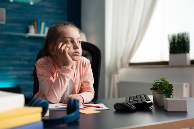 Dromerige scoolkid zit aan een bureau in de woonkamer en denkt aan creatieve trekking