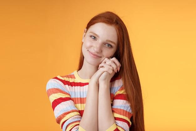 Dromerige sensuele romantische jonge gepassioneerde roodharige vriendin smelt hart voel sympathie vreugde ontvang zoete tedere aanwezig magere handpalmen glimlachend dankbaar accepteer graag leuk mooi cadeau, oranje achtergrond.