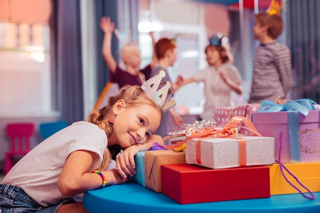 Dromerige sfeer. schattige kleine vrouw liggend op tafel terwijl ze droomt van zomervakantie