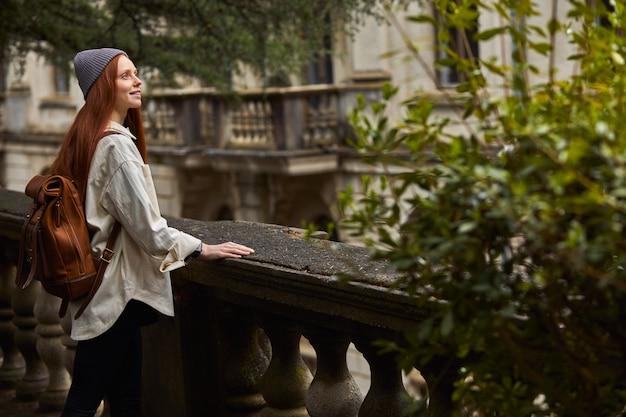 Dromerige sierlijke roodharige vrouw in jas met rugzak staande in oud gebouw op balkon vrouw is lo...