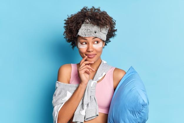 Dromerige tevreden jonge afro-amerikaanse vrouw kijkt opzij past collageen schoonheidspatches toe onder de ogen wordt wakker in een goed humeur houdt een zacht kussen vast