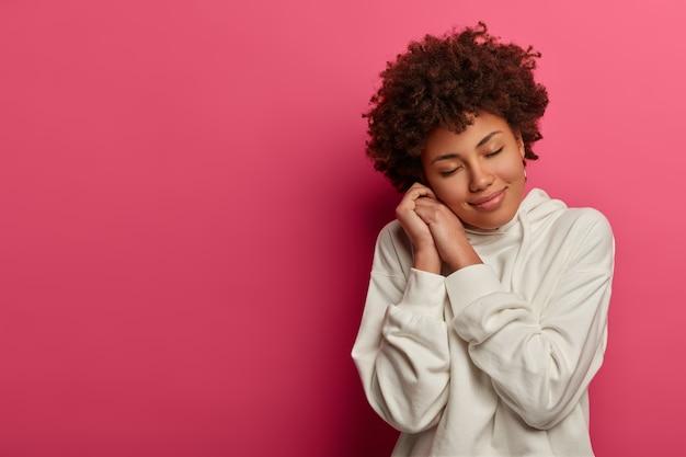 Dromerige tevreden vrouw met afro-krullend kapsel