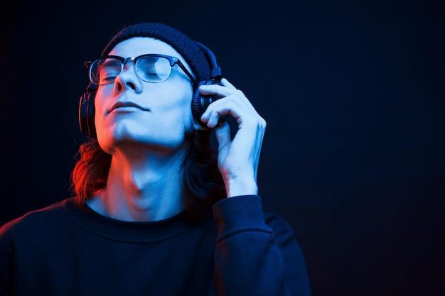 Dromerige uitstraling. studio opname in donkere studio met neonlicht. portret van ernstige man