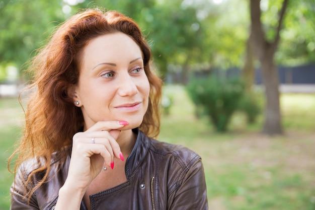 Dromerige vrij jonge dame wat betreft kin in stadspark