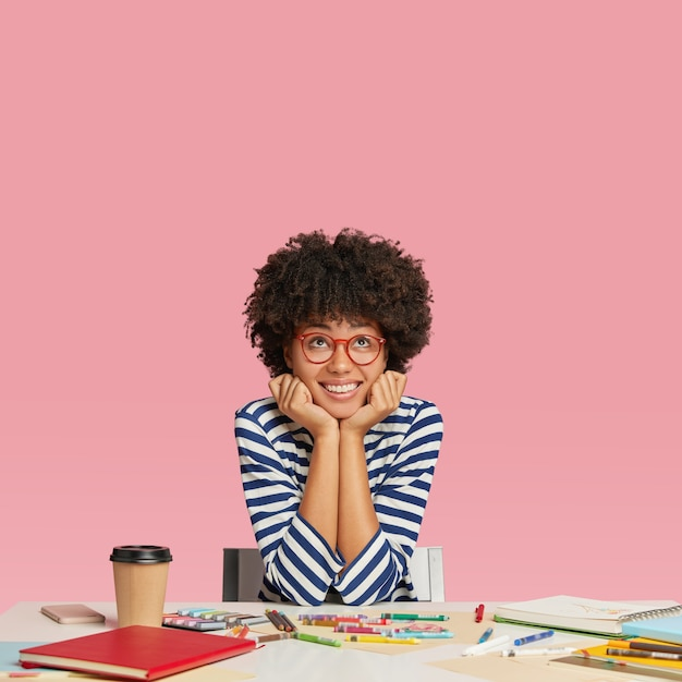 Dromerige vrolijke grafisch ontwerper denkt aan nieuw project