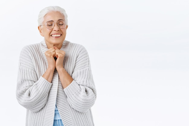 Dromerige, vrolijke oude vrouw die genegenheid en vreugde voelt, herinnert zich een mooie herinnering, drukt de handen tegen elkaar in de buurt van de borst, sluit de ogen en lacht opgewonden, blije kinderen komen thuis voor vakantie