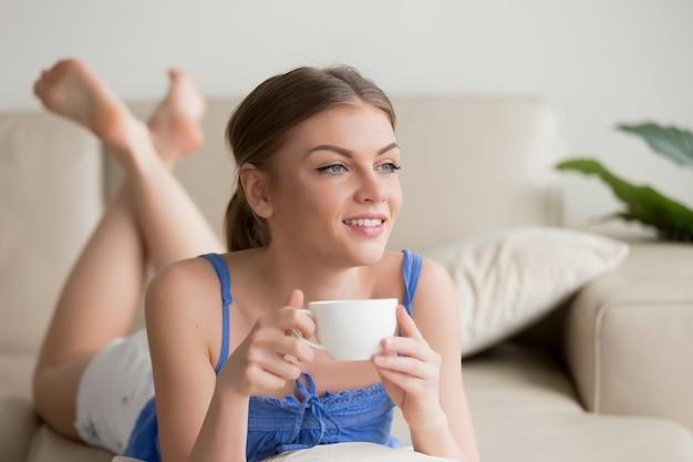 Dromerige vrouw die op comfortabele bank ontspant, die van kop van coffe geniet