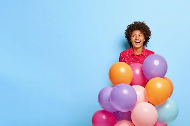 Dromerige vrouw houdt veelkleurige ballonnen vast tijdens het poseren