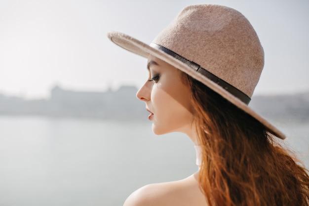 Dromerige vrouw met naakte make-up die naar beneden kijkt en aan iets denkt op de riviermuur