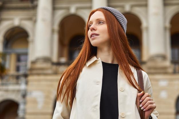 Dromerige vrouw met rood haar poseren en wandelen wandelen op de achtergrond van een oud historisch gebouw...