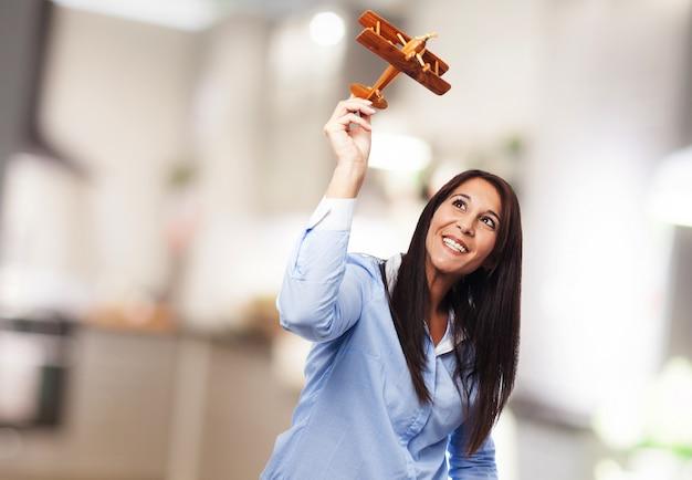 Dromerige vrouw spelen met een vliegtuig