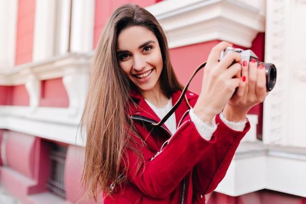 Dromerige vrouwelijke fotograaf met trendy manicure buiten werken en lachen