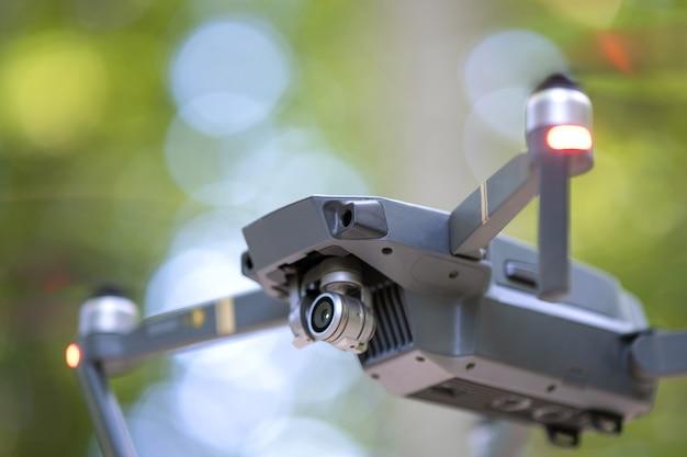 Drone copter met vage propellers en videocamera die in de lucht vliegt.