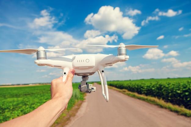 Drone in de hand voor een man op een achtergrond het groene veld