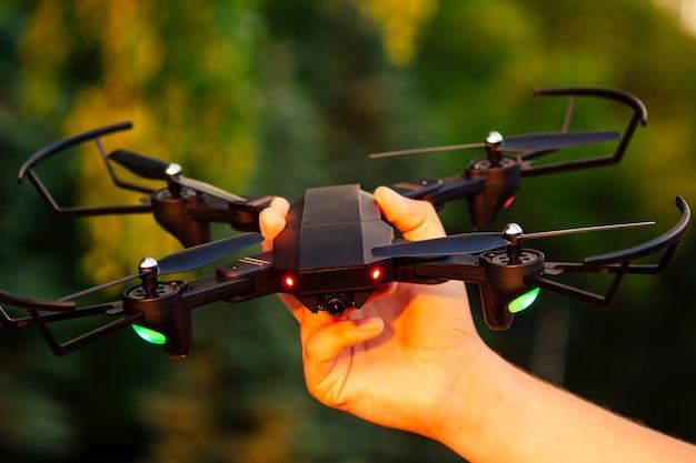 Drone op iemands hand op een groene achtergrond.