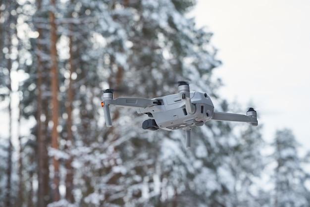 Drone quadcopter met camera vliegen in het woud van de winter