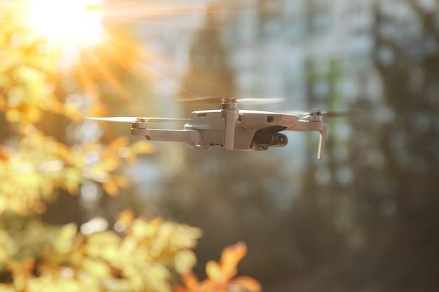 Drone quadrocopter met digitale camera en sensoren hoogvliegend bestuurd door piloot. helikopter drone vliegen binnenshuis. quad copter met verborgen camera die huis en tuin bespioneert. ruimte kopiëren