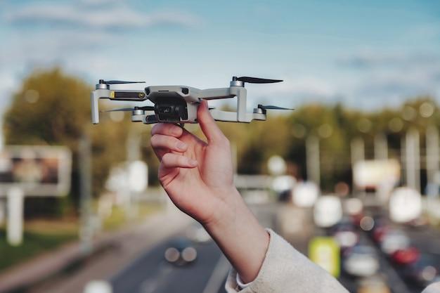 Drone quadrocopter opstijgen uit handen van de mens buitenshuis. jonge man die luchthelikopter loslaat om te vliegen met een kleine digitale vliegende camera. concept van moderne technologie in ons leven. ruimte voor site kopiëren