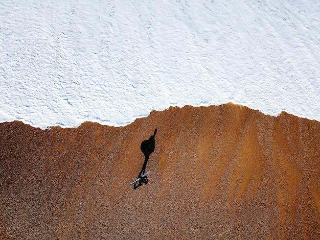 Drone shot van surfer die op de kustlijn loopt