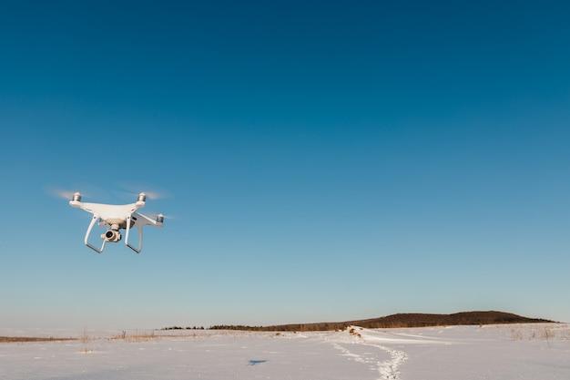 Drone vliegt boven veld bedekt met sneeuw op zonnige winterdag