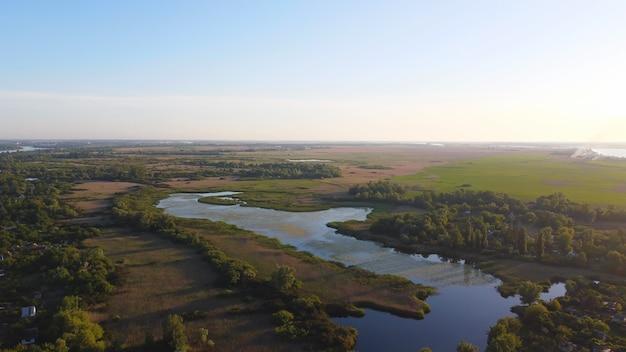 Drone vliegt over een golvende rivier van blauwe kleur, omringd door een lokaal dorp en een moerashabitat met gemeenschappelijk riet
