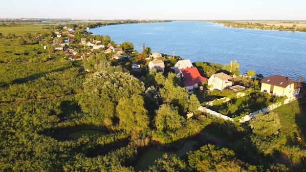 Drone vliegt over een golvende rivier van blauwe kleur, omringd door een lokaal dorp met verschillende gebouwen