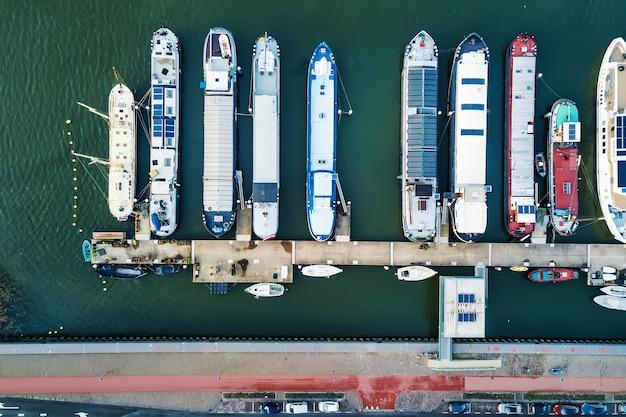 Drone-weergave van moderne schepen en boten drijvend op zeewater in de buurt van de kade in de stad