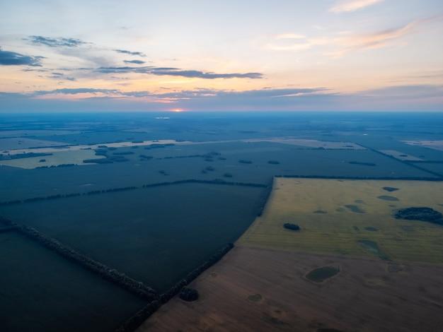 Dronefoto van velden met roggetarwe op het platteland met ondergaande zon op de achtergrond