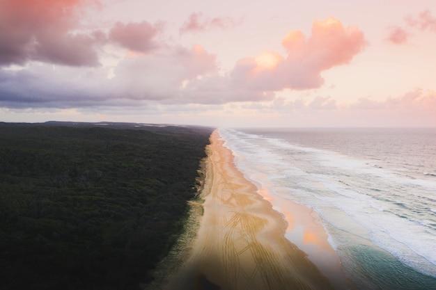 Dronezicht op de kustlijn onder een pastelroze lucht