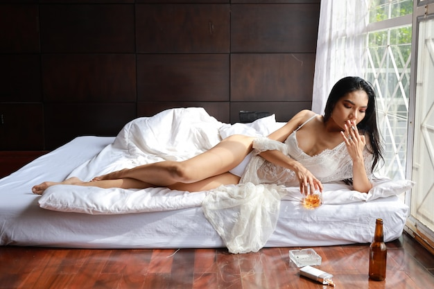 Dronken aziatische vrouw in witte lingerie, drinken en roken terwijl fles alcoholische drank en liggend op bed in de slaapkamer