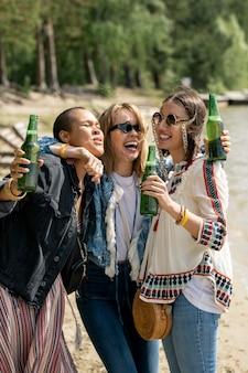Dronken blond-haired meisje omhelst vrienden en lachen terwijl ze bier drinkt met hen op het strand
