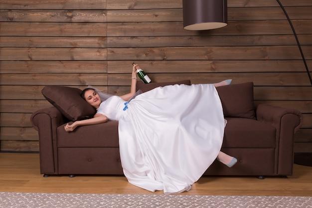 Dronken bruid met fles alcohol in de hand ontspannen op de bank na huwelijksfeest.