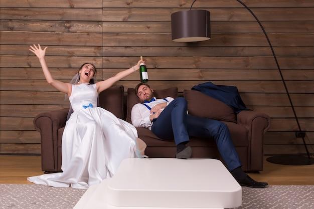 Dronken bruid met fles, bruidegom slapen op de bank