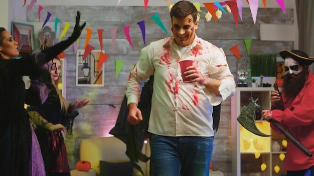 Dronken gevaarlijke zombie die halloween viert met andere griezelige personages die op de achtergrond dansen.