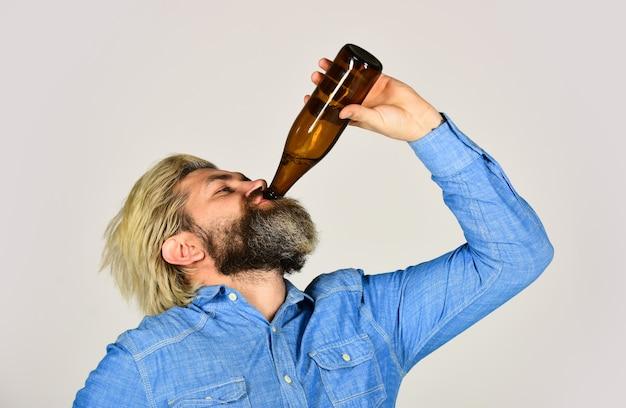 Dronken hipster mannelijk ambachtelijk gebotteld bier. gelukkige man houdt volle glazen fles in de hand. mannelijke bedrijf flesje bier. hipster rust in de kroeg. sportliefhebber vrolijk op. volwassen man met glazen flesje bier.