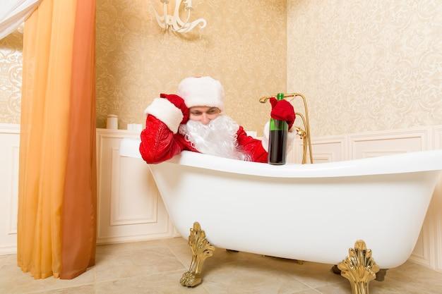 Dronken kerstman met fles slapen in een bad