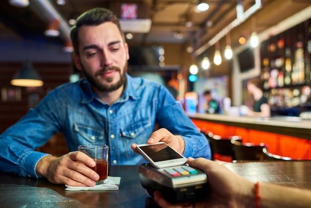Dronken man betalen via nfc in bar