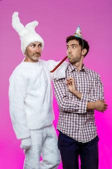 Dronken man en konijn op verjaardagsfeestje over paarse muur.