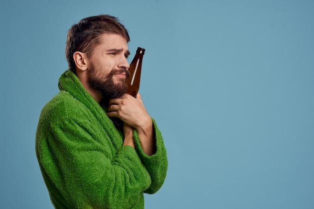 Dronken man in een groen gewaad met een flesje bier in zijn hand op blauw