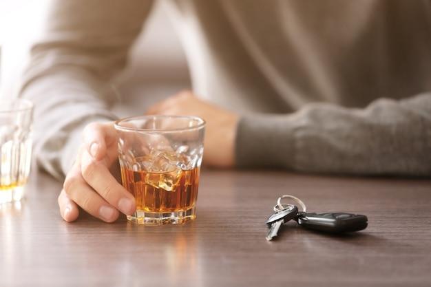 Dronken man met autosleutel en alcoholische drank in bar, close-up. niet drinken en rijden concept