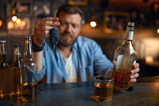 Dronken man met autosleutel zit aan de balie in de bar. een mannelijke persoon rust in de pub, menselijke emoties en vrijetijdsbesteding. een redelijke handeling, weigert te rijden onder invloed van alcohol