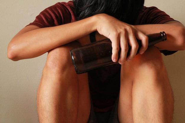 Dronken man met bierfles heeft stress in het leven en zit alleen in een lege kamer, verdrietig, eenzaam, school, adolescentie, huiselijk geweld, ongewenste liefdesproblemen, alleen, familie