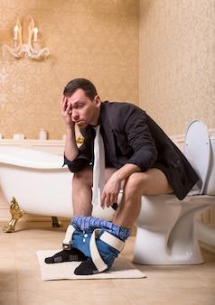 Dronken man met broek naar beneden zittend op de toiletpot. badkamer interieur in retro stijl