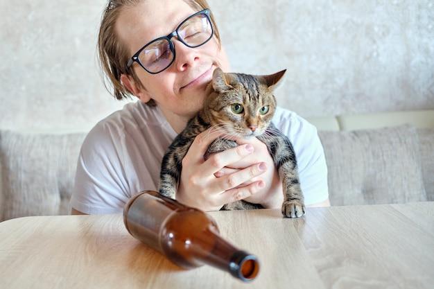 Dronken man met een fles knuffels een kat