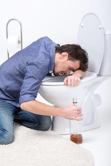 Dronken man met fles wijn in toilet.