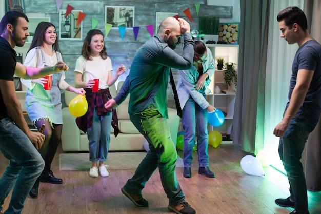 Dronken man op het feest van zijn vrienden die danspasjes doet.