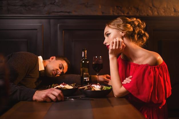 Dronken man slaapt aan tafel tegen vrouw