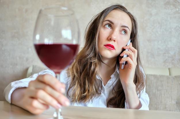 Dronken meisje drinkt wijn en praat op de smartphone.