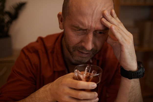 Dronken volwassen man die alcohol drinkt en op deze manier van zijn problemen afkomt